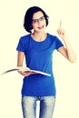 Studying happy young woman reading her notebook for school and pointing on copy space Stock Photo