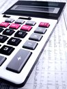 Studying stock market trends a photograph showing a finance calculator on top of a newspaper page with the list of stocks prices Stock Photo