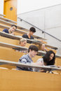 Studying students in a lecture hall sitting while learning and taking notes Royalty Free Stock Images