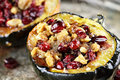 Stuffed acorn squash and baked with brown sugar walnuts and cranberries ready for holiday dinners extreme shallow depth of field Stock Image