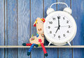 Stuffed animal giraffe and clock for bedtime sitting next to alarm at seven o isolated over white background Royalty Free Stock Image