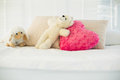 Stuffed animals and a heart pillow lying on couch in living room Royalty Free Stock Photos