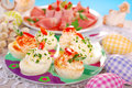Stuffed eggs with cheese and mayonnaise for easter egg halves decorated red pepper chives Royalty Free Stock Photos