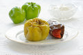 Stuffed pepper and aubergine on a white plate with green bell peppers and natural yoghurt on the background Stock Photos