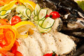 Stuffed pike with head sliced decorated tomato lemon and cucumber close up in restaurant Stock Photo