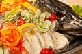 Stuffed pike with head sliced decorated tomato lemon and cucumber close up in restaurant Stock Photos