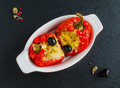 Stuffed red sweet peppers with feta cheese and olives in baking dish on black stone background, top view Royalty Free Stock Photo