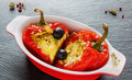Stuffed red sweet peppers with feta cheese and olives in red and white baking dish on black stone background Royalty Free Stock Photo