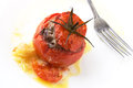 Stuffed tomato white plate with cooked tomatoe with minced meat with sauce fork and knife on the background Royalty Free Stock Image