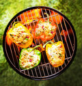 Stuffed veggy bell peppers grilling on a bbq view from above of colorful red green and yellow savory with glowing hot coals Royalty Free Stock Image