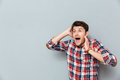Stunned afraid young man in checkered shirt standing and shouting Royalty Free Stock Photo