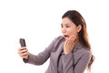 Stunned business woman receiving bad news from her smart phone exited or mobile Royalty Free Stock Photo