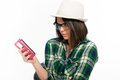 Stunned look at message young woman with hat and eyeglasses looking her smartphone studio shot Royalty Free Stock Photos