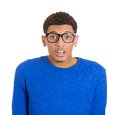 Stunned nerd man closeup portrait of truly young open mouth jaw drop in blue shirt and big glasses isolated on white background Royalty Free Stock Images