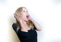 Stunned young woman on white portrait beautiful blonde astonished hands head and open mouth looking up Stock Photos