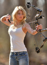 Stunning blonde female archer young woman in white tank top and jeans shooting a compound bow archery arrow shown leaving bow Stock Photos