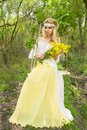 Stunning blonde sexy natural woman swing on a swing on a tree wearing a spring dress Royalty Free Stock Photo