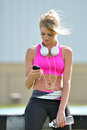 Stunning blonde woman fitness model young in pink sports bra rests while holding a water bottle and adjusting music on portable Stock Photos
