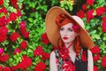 Stunning girl with red lips in dress with a print of roses on a beautiful summer background. Young redhead model in hat on a backg