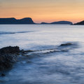 Stunning landscape dawn sunrise with rocky coastline and long exp over beautiful in mediterranean sea Stock Photo