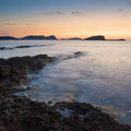 Stunning landscape dawn sunrise with rocky coastline and long exp over beautiful in mediterranean sea Stock Photos