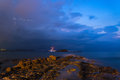 Stunning landscape with storm and lightning dawn with rocky coas over beautiful coastline in mediterranean sea Royalty Free Stock Photo