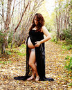 Stunning pregnant woman in fall pose posing on nature path Royalty Free Stock Photography