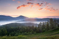 Stunning sunrise mountain landscape with beautiful fog and cloud vibrant colors clouds formations summer time Stock Images