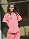 Stunning young african american female healthcare worker professional in pink scrubs standing in front of an office building or Stock Photo