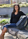 Stunning young african american female student on campus sitting a bench in the shade with a backpack smiling at viewer Stock Photo