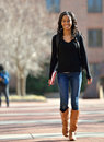 Stunning young african american female student on campus walking with backpack and boot outside Royalty Free Stock Photos
