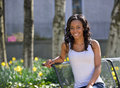 Stunning young african american woman white tank portrait of a in top outdoors in late afternoon sun seated in a park Royalty Free Stock Photography