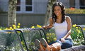 Stunning young african american woman white tank portrait of a in top outdoors in late afternoon sun seated in a park with feet on Royalty Free Stock Photo