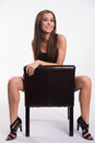 Stunning young beautiful barefoot woman straddles black leather shot from above straddling common chair Royalty Free Stock Photography