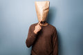 Stupid young man with bag over his head standing a Stock Images