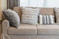 Sturdy brown sofa with grey patterned pillows Royalty Free Stock Photo