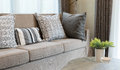 Sturdy brown tweed sofa with grey patterned pillows in living room Royalty Free Stock Images