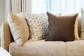 Sturdy brown tweed sofa with grey patterned pillows in living room Stock Photography