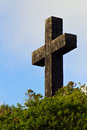 Sturdy stone cross rising from brush on a hilltop Royalty Free Stock Images