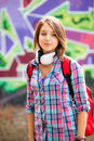 Style teen girl with backpack standing near graffiti wall Stock Photography