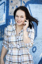 Style teen girl calling by phone near graffiti background. Royalty Free Stock Photo