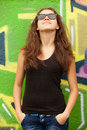 Style teen girl in sunglasses near graffiti background. Royalty Free Stock Images