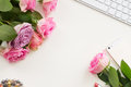 Styled desktop scene flat with mobile and flowers copy space on white table Royalty Free Stock Photos