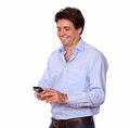 Stylish adult man texting on cellphone portrait of a while standing white background Stock Images
