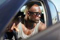 Stylish african young man in his car male model with hands on steering wheel muscular wearing sunglasses looking away Royalty Free Stock Photos