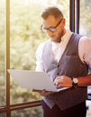 Stylish Bearded Businessman Wearing Glasses White Shirt Waistcoat Working Modern Laptop Holding Hands Near Panoramic Royalty Free Stock Photo