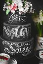 Stylish black wedding cake with flowers and the lettering love at candy bar Royalty Free Stock Photo