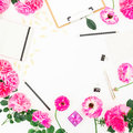 Stylish blogger workspace with clipboard, notebook, pink flowers and accessories on white background. Flat lay, top view.