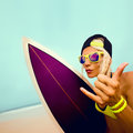 Stylish blond  on the beach with bright surf board. Surfing time Royalty Free Stock Photo
