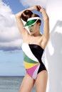 Stylish blond girl posing wearing beachwear and sunshade colorful shot Royalty Free Stock Photos